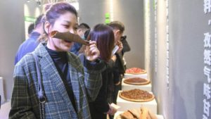 woman smelling ingredient at latiao museum in china