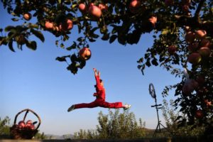 girl making video dancing in apple orchard in china