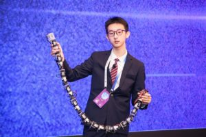student holding mechanical snake in china