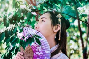 Hua Mulan: chinese girl under a tree holding a paper fan to her face