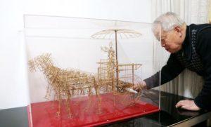 elderly craftsman next to bamboo terracotta warriors model in glass box