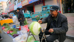 vegetable seller peeling vegetable on street in china