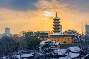 Winter in China: photo of sun setting behind pagoda covered in snow