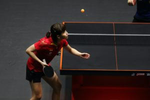 Chinese Champions: chinese female badminton player serving a ball