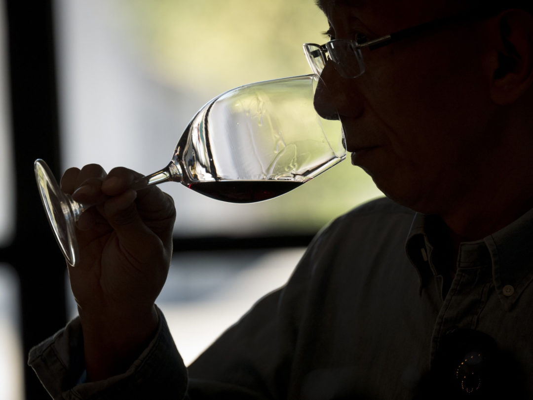 asian man drinking glass of red wine