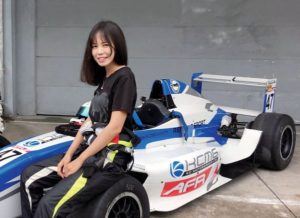 chinese driver gui meng sitting on racing car