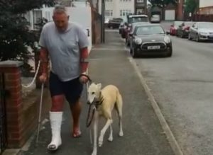 man with injured leg walking dog down the street
