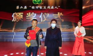 man collecting award on stage in china