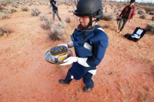 man carrying asteroid sample from landed spacecraft