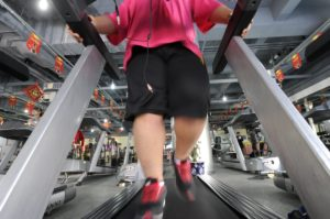 floor view of overweight asian person on running machine at gym