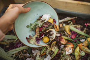 plate pouring leftover food into food waste bin