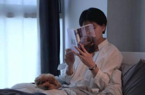 woman lying in bed with dog and reading a book