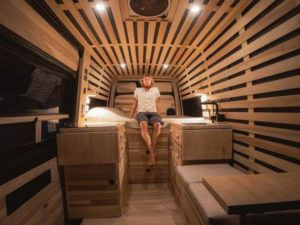 man sitting on bed in van converted into home