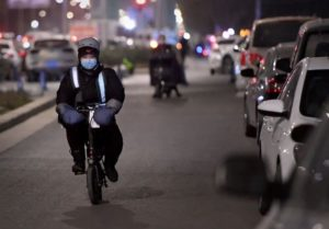 front view of woman on bike travelling down road in china