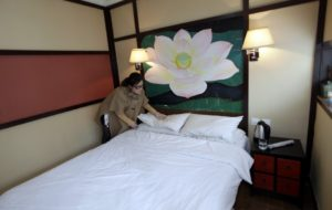 woman arranging pillow on hotel bed