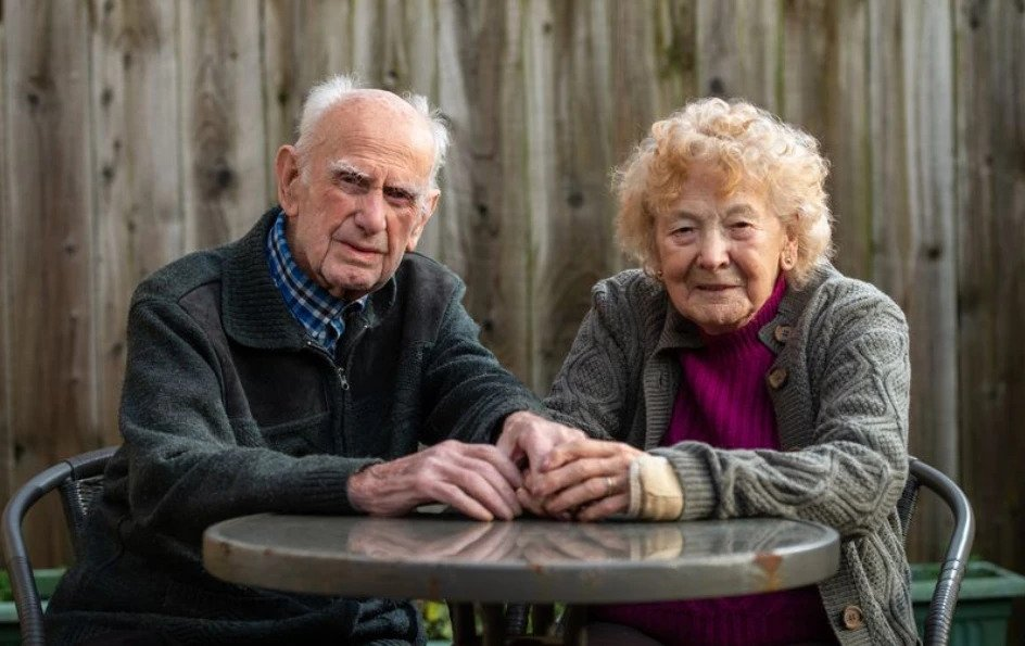 elderly couple posing for picture in garden