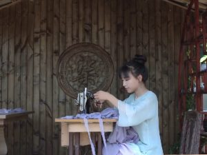 Chinese Influencers: Chinese influencers Li Ziqi sewing at a table