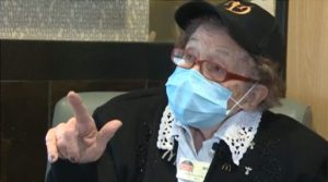 elderly woman wearing face mask and giving interview