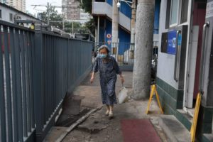 front view of elderly woman carrying bad while walking in china