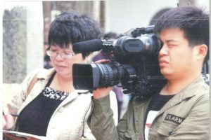 woman taking notes next to cameraman in china