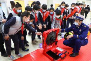 fireman showing children equipment at school in china