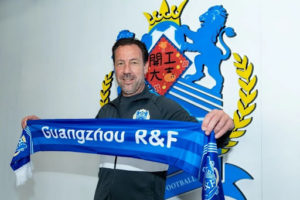 van gastel holding guangzhou city scarf and standing in front of team badge