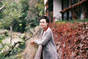 woman posing for picture outside in chinese countryside
