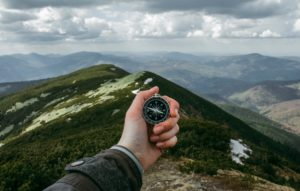 giving directions: hand holding a compass in front of a mountain