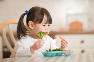 young asian girl eating vegetables at table