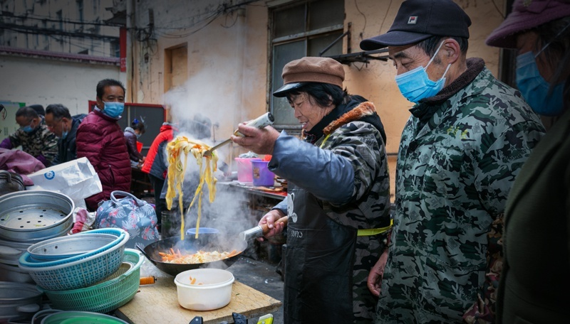 woman cooking at kitchen outside hospital in china