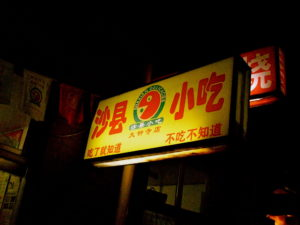 Shaxian Snacks restaurant sign lit up at night