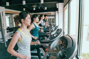 side view of line of women running at gym in china