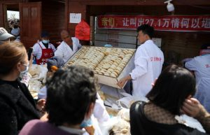 people crowding around steamed bread stall in china