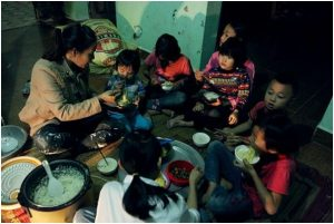 mother with children eating meal in vietnam