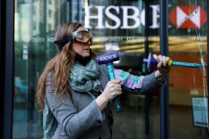 activist breaking glass with hammer outside HSBC head office in london