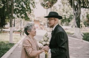 side view of elderly couple facing each other and holding flowers