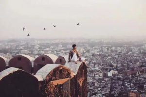 travel blogger sitting on top of building overlooking city