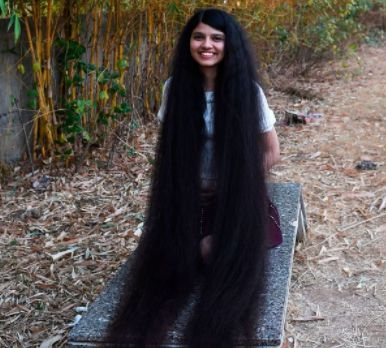 indian girl with long hair sitting outside