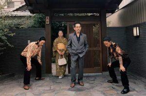 japanese family posing for photo outside home