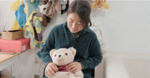 woman sitting with teddy bear in toy repair workshop