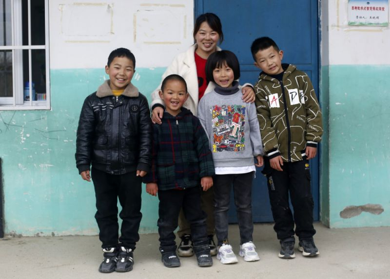 teacher posing for picture with students at village school in china
