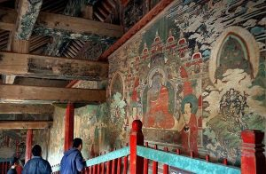 tourists viewing mural painting at qutan temple