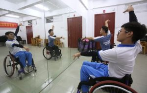 wheel chair users practicing dancing in front of a mirror in china