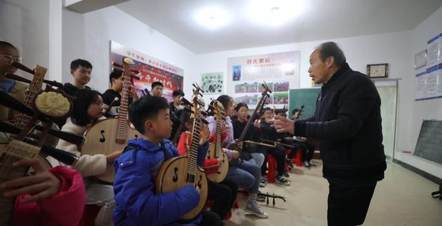 teacher giving music class at rural school in china