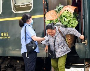 train attendant helping woman carrying vegetables off train in china