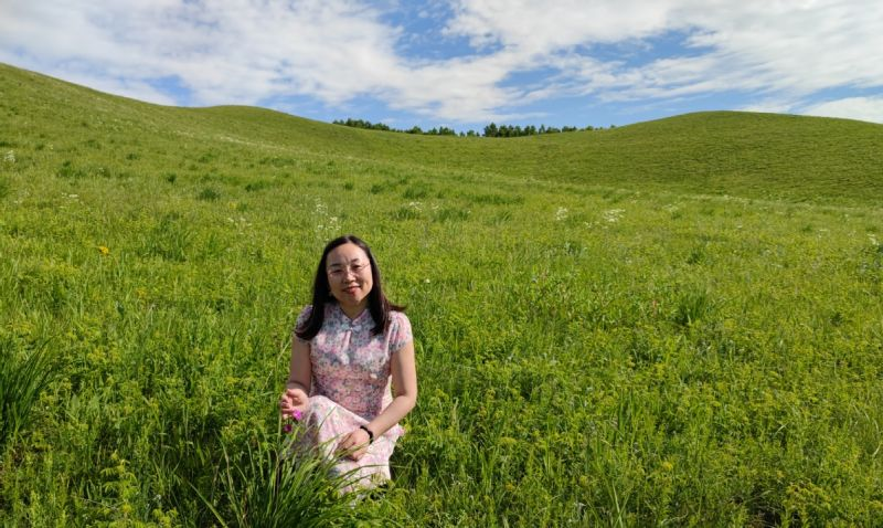 woman posing for picture in field on sunny day