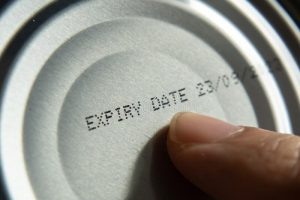 finger pointing to expiry date on bottom of can