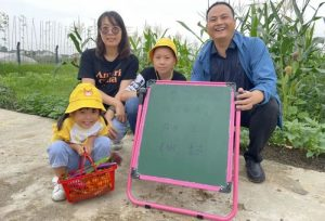 family posing for photo together with scoreboard for game in china