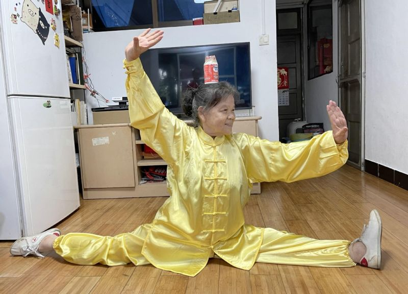 elderly woman practicing tai chi at home in china