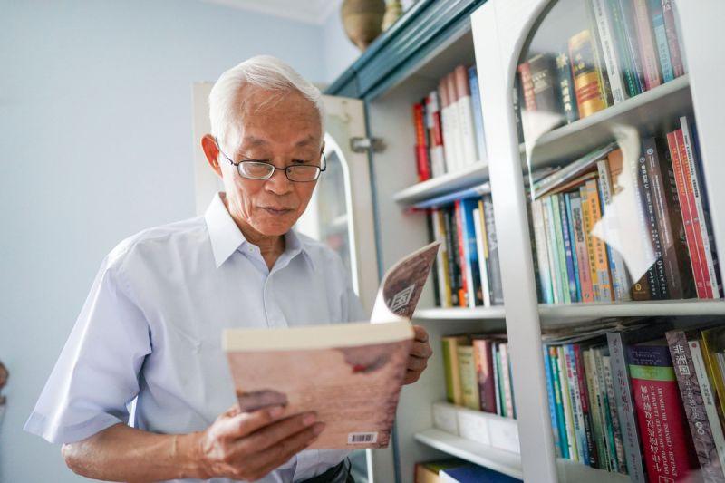 former chinese ambassador liu guijin reading book next to bookshelf at home